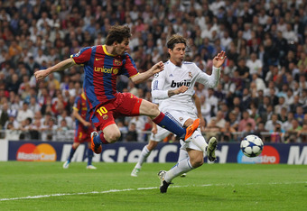 MADRID, SPAIN - APRIL 27:  Lionel Messi of Barcelona beat Sergio Ramos of Real Madrid to score the opening goal during the UEFA Champions League Semi Final first leg match between Real Madrid and Barcelona at Estadio Santiago Bernabeu on April 27, 2011 in