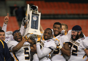 WASHINGTON, DC - DECEMBER 28: Diauntae Morrow #5 and Desmond Marrow #3 of the Toledo Rockets hold up the championship trophy after the Rockets defeated the Air Force Falcons 42-41 to win the Military Bowl at RFK Stadium on December 28, 2011 in Washington,