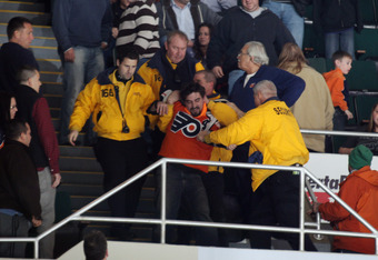 UNIONDALE, NY - NOVEMBER 23:  Security guards tussle with a fan during the game between the Philadelphia Flyers and the New York Islanders at the Nassau Veterans Memorial Coliseum on November 23, 2011 in Uniondale, New York.  (Photo by Bruce Bennett/Getty