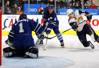 TORONTO - APRIL 1:  Patrick Kaleta #36 of the Buffalo Sabres gets a shot off as he falls while Andrew Raycroft #1 of the Toronto Maple Leafs positions himself to make a save and Kris Newbury #54 of the Toronto Maple Leafs looks on during their NHL game at