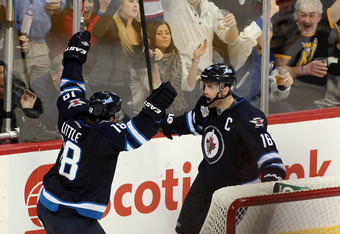 WINNIPEG, CANADA - DECEMBER 6: Bryan Little #18 and Andrew Ladd #16 celebrate Little's game winning goal against the Boston Bruins in NHL action at the MTS Centre on December 6, 2011 in Winnipeg, Manitoba, Canada. (Photo by Marianne Helm/Getty Images)
