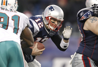 FOXBORO, MA - DECEMBER 24:  Tom Brady #12 of the New England Patriots sneaks past Cameron Wake #91 of the Miami Dolphins during the second half of New England's 27-24 win at Gillette Stadium on December 24, 2011 in Foxboro, Massachusetts.  (Photo by Winsl