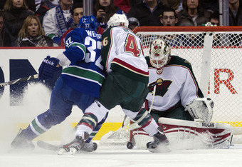 VANCOUVER, CANADA - DECEMBER 19: Goalie Niklas Backstrom #32 of the Minnesota Wild makes a save while Dale Weise #32 of the Vancouver Canucks and Jared Spurgeon #46 battle for position during the first period in NHL action on December 19, 2011 at Rogers A