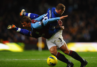BIRMINGHAM, ENGLAND - DECEMBER 03:  Stephen Warnock of Aston Villa and Wayne Rooney of Manchester United clash during the Barclays Premier League match between Aston Villa and Manchester United at Villa Park on December 3, 2011 in Birmingham, England.  (P