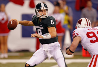 INDIANAPOLIS, IN - DECEMBER 03:  Kirk Cousins #8 of the Michigan State Spartans looks to pass under pressure from Pat Muldoon #92 of the Wisconsin Badgers during the Big 10 Conference Championship Game at Lucas Oil Stadium on December 3, 2011 in Indianapo