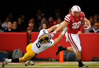 LINCOLN, NE - NOVEMBER 25: Running back Rex Burkhead #22 of the Nebraska Cornhuskers stiff-arms defensive back Tanner Miller #5 of the Iowa Hawkeyes during their game at Memorial Stadium November 25, 2011 in Lincoln, Nebraska. (Photo by Eric Francis/Getty