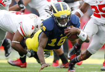 ANN ARBOR, MI - NOVEMBER 26:  Denard Robinson #16 of the Michigan Wolverines dives for extra yards past C.J. Barnett #4 of the Ohio State Buckeyes at Michigan Stadium on November 26, 2011 in Ann Arbor, Michigan. Michigan won the game 40-34. (Photo by Greg