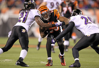 CINCINNATI, OH - JANUARY 01:  Jerome Simpson #89 of the Cincinnati Bengals runs with the ball while tackled by Lardarius Webb #21 and Ed Reed #20 of the Baltimore Ravens during the NFL game at Paul Brown Stadium on January 1, 2012 in Cincinnati, Ohio.  (P