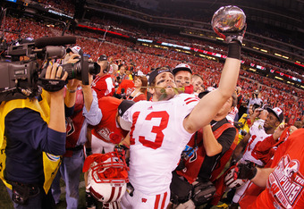 INDIANAPOLIS, IN - DECEMBER 03:  Conor O'Neill #13 of the Wisconsin Badgers celebrates with the trophy after they won 42-39 against the Michigan State Spartans\ during the Big 10 Conference Championship Game at Lucas Oil Stadium on December 3, 2011 in Ind