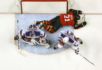 SUNRISE, FL - DECEMBER 30: Ryan McDonagh #27 of the New York Rangers assists goaltender Henrik Lundqvist #30 defend the net as Krystofer Barch #21 of the Florida Panthers lies in the crease area after tripping on December 30, 2011 at the BankAtlantic Cent