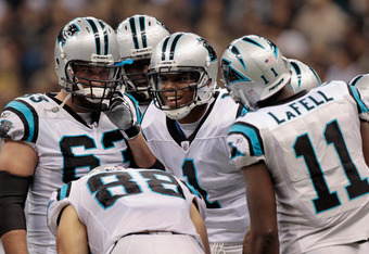 NEW ORLEANS, LA - JANUARY 01:   Cam Newton #1 of the Carolina Panthers talks to his team in the huddle while playing the New Orleans Saints at the Mercedes-Benz Superdome on January 1, 2012 in New Orleans, Louisiana.  (Photo by Chris Graythen/Getty Images