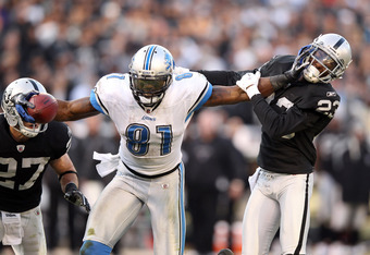 OAKLAND, CA - DECEMBER 18:  Calvin Johnson #81 of the Detroit Lions tries to break free from DeMarcus Van Dyke #23 of the Oakland Raiders at O.co Coliseum on December 18, 2011 in Oakland, California.  (Photo by Ezra Shaw/Getty Images)