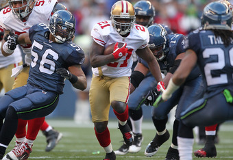 SEATTLE - DECEMBER 24:  Running back Frank Gore #21 of the San Francisco 49ers rushes against Leroy Hill #56 of the Seattle Seahawks at CenturyLink Field on December 24, 2011 in Seattle, Washington. The 49ers defeated the Seahawks 19-17. (Photo by Otto Gr