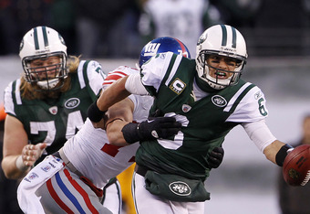 EAST RUTHERFORD, NJ - DECEMBER 24:  Mark Sanchez #6 of the New York Jets is grabbed then sacked by by Dave Tollefson #71 of the New York Giants during the third quarter of a game at MetLife Stadium on December 24, 2011 in East Rutherford. New Jersey. (Pho