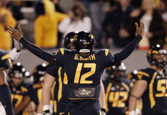 MORGANTOWN, WV - NOVEMBER 25:  Geno Smith #12 of the West Virginia Mountaineers gestures to his team prior to the Backyard Brawl against the University of Pittsburgh Panthers on November 25, 2011 at Mountaineer Field in Morgantown, West Virginia.  (Photo
