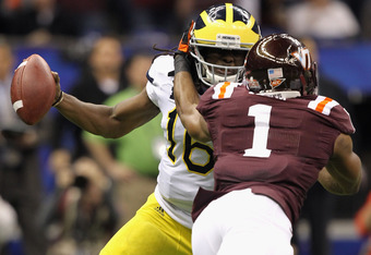 NEW ORLEANS, LA - JANUARY 03:  Denard Robinson #16 of the Michigan Wolverines attempts to break away from pressure from Antone Exum #1 of the Virginia Tech Hokies during the Allstate Sugar Bowl at Mercedes-Benz Superdome on January 3, 2012 in New Orleans,