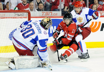 CALGARY, CANADA - JANUARY 3:  Andrei Vasilevski #30 of Team Russia stops the puck on an attempt by Jonathan Huberdeau #11 of Team Canada during the 2012 World Junior Hockey Championship Semifinal game at the Saddledome on January 3, 2012 in Calgary, Alber