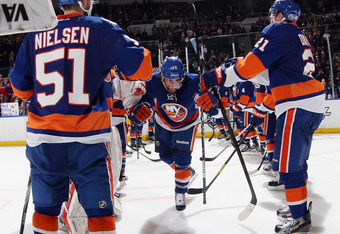 UNIONDALE, NY - DECEMBER 31: Matt Moulson #26 of the New York Islanders skates through the line of players after being named one of the stars of the game following a 4-1 victory over the Edmonton Oilers at the Nassau Veterans Memorial Coliseum on December
