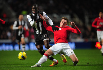 NEWCASTLE UPON TYNE, ENGLAND - JANUARY 04:  Newcastle forward Demba Ba is tackled by Phil Jones during the Barclays Premier league game between Newcastle United and Manchester United at St James' Park on January 4, 2012 in Newcastle upon Tyne, England.  (