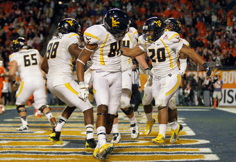 MIAMI GARDENS, FL - JANUARY 04:  (L-R) Will Clarke #98, J.D. Woods #81 and Shawne Alston #20 of the West Virginia Mountaineers celebrates with teamates after Alston scored a 1-yard rushing touchdown in the second quarter against the Clemson Tigers  during