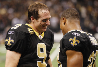 NEW ORLEANS, LA - DECEMBER 26:  Quarterback Drew Brees #9 of the New Orleans Saints celebrates with Pierre Thomas #23 after Brees throws a nine-yard touchdown pass to running back Darren Sproles #43 and breaks the single-season passing record in the fourt