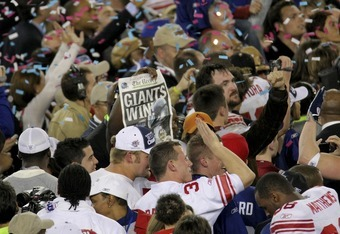 GLENDALE, AZ - FEBRUARY 03:  Players from the New York Giants celebrate with with a copy of the Bergen Record with the headline 'Giants Win' following their 17-14 win against the New England Patriots during Super Bowl XLII on February 3, 2008 at the Unive
