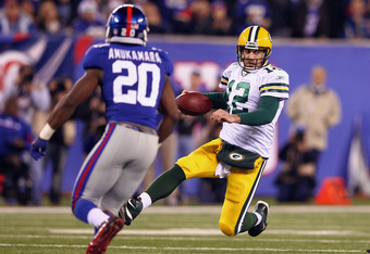 EAST RUTHERFORD, NJ - DECEMBER 04:  Aaron Rodgers #12 of the Green Bay Packers slides to the turf against Prince Amukamara #20 of the New York Giants at MetLife Stadium on December 4, 2011 in East Rutherford, New Jersey.  (Photo by Al Bello/Getty Images)