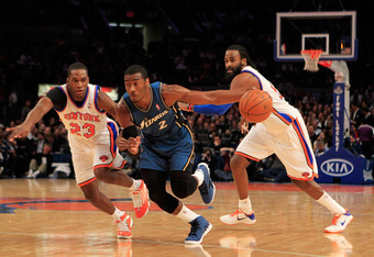 NEW YORK, NY - JANUARY 24: John Wall #2 of the Washington Wizards drives past  Toney Douglas #23 of the New York Knicks at Madison Square Garden on January 24, 2011 in New York City. NOTE TO USER: User expressly acknowledges and agrees that, by downloadin