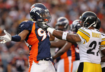 DENVER - AUGUST 29:  Linebacker Jarvis Moss #94 of the Denver Broncos and cornerback Joe Burnett #27 of the Pittsburgh Steelers mix it up during preseason NFL action at INVESCO Field at Mile High on August 29, 2010 in Denver, Colorado.  (Photo by Doug Pen