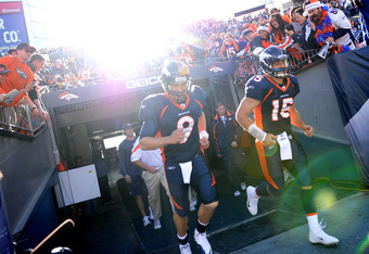 DENVER, CO - DECEMBER 18: Quarterbacks Tim Tebow #15 and Brady Quinn #9 of the Denver Broncos take the field during warm ups before playing the New England Patriots at Sports Authority Field at Mile High on December 18, 2011 in Denver, Colorado. (Photo by