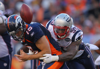 DENVER, CO - DECEMBER 18:  Quarterback Tim Tebow #15 of the Denver Broncos fumbles the ball as he is hit by defensive end Mark Anderson #95 of the New England Patriots who recovered the ball on the play at Sports Authority Field at Mile High on December 1