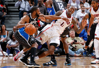 ATLANTA, GA - APRIL 28:  Jamal Crawford #11 of the Atlanta Hawks draws an offensive foul as he is forced to the floor while defending against Gilbert Arenas #1 of the Orlando Magic during Game Six of the Eastern Conference Quarterfinals in the 2011 NBA Pl