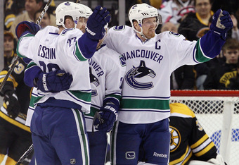 BOSTON, MA - JANUARY 07:  Henrik Sedin #33 and Daniel Sedin #22 of the Vancouver Canucks celebrate a goal in the first period against the Boston Bruins on January 7, 2012 at TD Garden in Boston, Massachusetts.  (Photo by Elsa/Getty Images)
