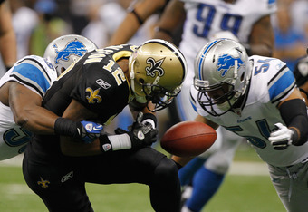 NEW ORLEANS, LA - JANUARY 07:   Marques Colston #12 of the New Orleans Saints fumbles the ball while being tackled by Stephen Tulloch #55 and  DeAndre Levy #54 of the Detroit Lions during their 2012 NFC Wild Card Playoff game at Mercedes-Benz Superdome on