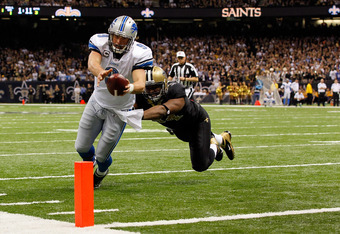 NEW ORLEANS, LA - JANUARY 07:  Matthew Stafford #9 of the Detroit Lions dives for the touchdown against Will Smith #91 of the New Orleans Saints during their 2012 NFC Wild Card Playoff game at Mercedes-Benz Superdome on January 7, 2012 in New Orleans, Lou