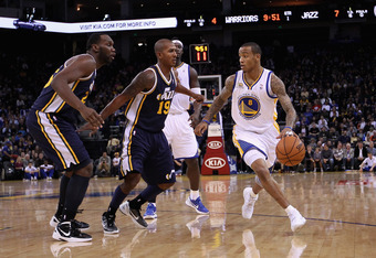 OAKLAND, CA - JANUARY 07:  Monta Ellis #8 of the Golden State Warriors dribbles the ball while guarded by Raja Bell #19 and Al Jefferson #25 of the Utah Jazz at Oracle Arena on January 7, 2012 in Oakland, California.  NOTE TO USER: User expressly acknowle