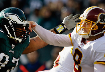 PHILADELPHIA, PA - JANUARY 01:  Rex Grossman #8 of the Washington Redskins hits the helmet of  Cullen Jenkins #97 of the Philadelphia Eagles after throwing a first half pass at Lincoln Financial Field on January 1, 2012 in Philadelphia, Pennsylvania.  (Ph
