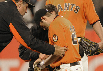 SAN FRANCISCO, CA - JUNE 10: Manager Bruce Bochy (L) of the San Francisco Giants helps injured second baseman Freddy Sanchez #21 up and off the field as Pat Burrell #5 looks on against the Cincinnati Reds during a MLB baseball game June 10, 2011 at AT&T P