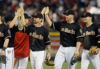 PHOENIX, AZ - SEPTEMBER 24:  Ryan Roberts #14 of the Arizona Diamondbacks and Lyle Overbay #37 high-five teammates following their 15-2 victory over the San Francisco Giants during a Major League Baseball game at Chase Field on September 24, 2011 in Phoen