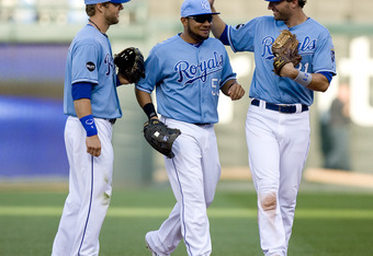 KANSAS CITY, MO - SEPTEMBER 14:   Alex Gordon #4 of the Kansas City Royals, Melky Cabrera #53 and Jeff Francoeur #21 celebrate a 7-3 win over the Minnesota Twins at Kauffman Stadium on September 14, 2011 in Kansas City, Missouri. (Photo by Ed Zurga/Getty