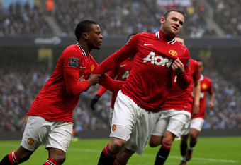 MANCHESTER, ENGLAND - JANUARY 08:  Wayne Rooney of Manchester United celebrates scoring the opening goal with Patrice Evra (L) during the FA Cup Third Round match between Manchester City and Manchester United at the Etihad Stadium on January 8, 2012 in Ma