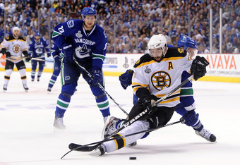 VANCOUVER, BC - JUNE 15:  Patrice Bergeron #37 of the Boston Bruins falls to the ice as he scores the 3rd goal in the second period against Roberto Luongo #1 of the Vancouver Canucks during Game Seven of the 2011 NHL Stanley Cup Final at Rogers Arena on J