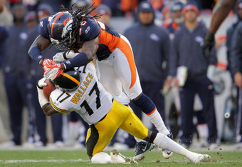 DENVER, CO - JANUARY 08:  Mike Wallace #17 of the Pittsburgh Steelers makes a reception on third down and ten yards to go but is stopped short of the first down by Quinton Carter #28 of the Denver Broncos at Sports Authority Field at Mile High on January