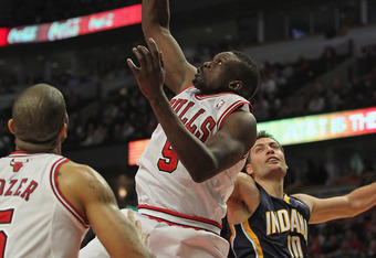 CHICAGO, IL - DECEMBER 20:  Loul Deng #9 of the Chicago Bulls grabs a rebound over Carlos Boozer #5 and Jeff Foster #10 of the Indiana Pacers at the United Center on December 20, 2011 in Chicago, Illinois. The Bulls defeated the Pacers 93-85. NOTE TO USER