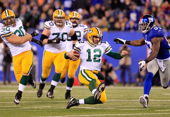EAST RUTHERFORD, NJ - DECEMBER 04:  Aaron Rodgers #12 of the Green Bay Packers slides to the turf as he runs the ball against Jacquian Williams #57 of the New York Giants at MetLife Stadium on December 4, 2011 in East Rutherford, New Jersey. The Packers w