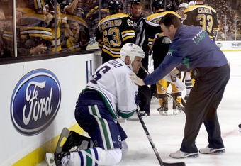 BOSTON, MA - JANUARY 07:  Sami Salo #6 of the Vancouver Canucks is helped off the ice after he was hit by Brad Marchand #63 of the Boston Bruins on January 7, 2012 at TD Garden in Boston, Massachusetts.  (Photo by Elsa/Getty Images)