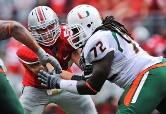 COLUMBUS, OH - SEPTEMBER 11:  John Simon #54 of the Ohio State Buckeyes is blocked by Brandon Washington #72 of the Miami Hurricanes at Ohio Stadium on September 11, 2010 in Columbus, Ohio.  (Photo by Jamie Sabau/Getty Images)