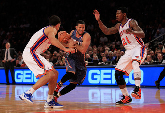 NEW YORK, NY - JANUARY 09:  (C) D.J. Augustin #14 of the Charlotte Bobcats is challenged by (L) Landry Fields #2 of the New York Knicks and (R) Iman Shumpert #21 of the New York Knicks at Madison Square Garden on January 9, 2012 in New York City. NOTE TO