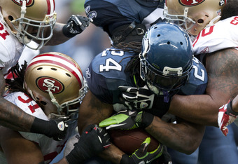 SEATTLE, WA - DECEMBER 12:  Marshawn Lynch #24 of the Seattle Seahawks is tackled by members of the San Francisco 49ers defense at CenturyLink Field December 24, 2011 in Seattle, Washington. San Francisco won 19-17. (Photo by Jay Drowns/Getty Images)