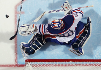 UNIONDALE, NY - DECEMBER 31: Devan Dubnyk #40 of the Edmonton Oilers makes the save on Frans Nielsen #51 of the New York Islanders at the Nassau Veterans Memorial Coliseum on December 31, 2011 in Uniondale, New York. The Islanders defeated the Oilers 4-1.